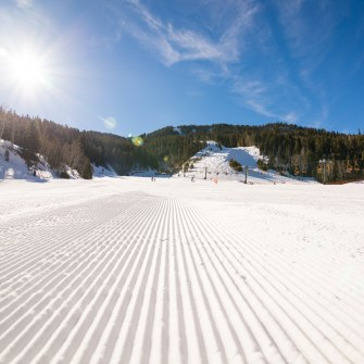 ski slope with sun and blue sky