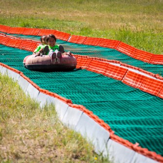kids riding down summer mountain tubing