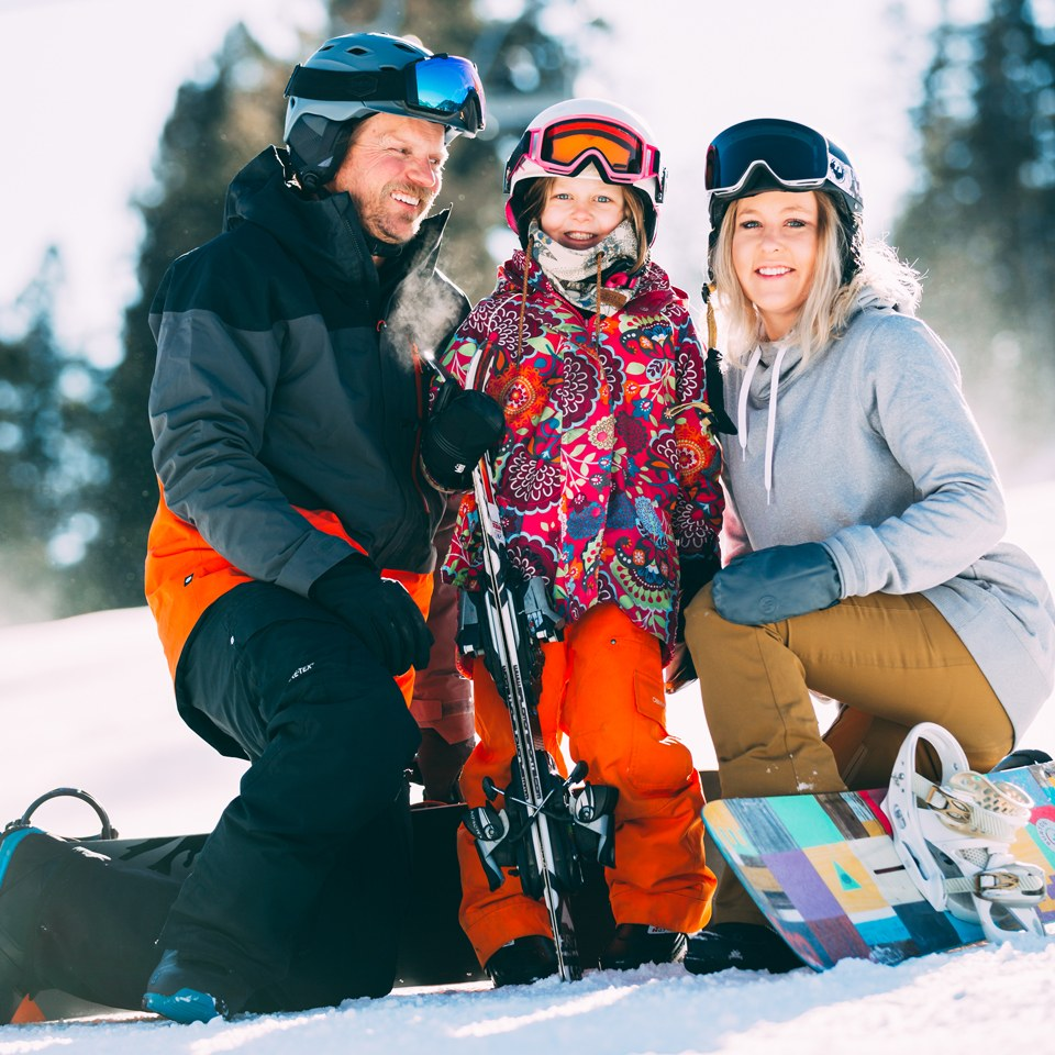 family with ski and snowboard equipment