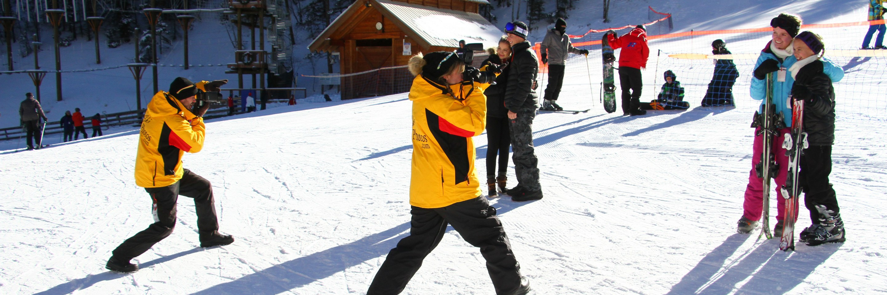 photographers taking photos of people skiing