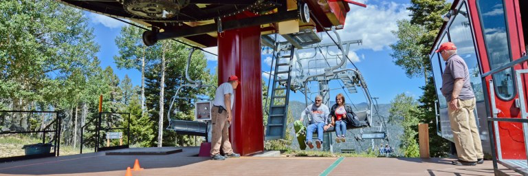 Couple unloading scenic summer chairlift ride at the top