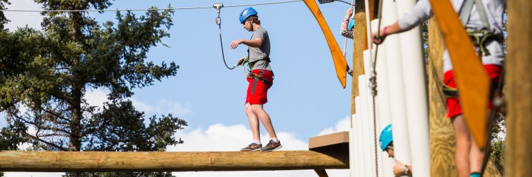 Man balancing on  Aerial Park element - summer vacation getaways in New Mexico