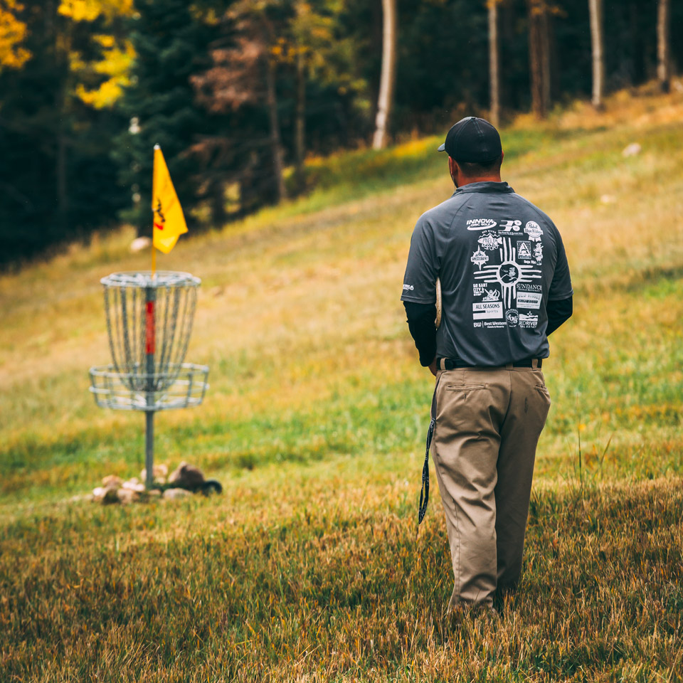 disc golfer standing near basket about to throw a putt