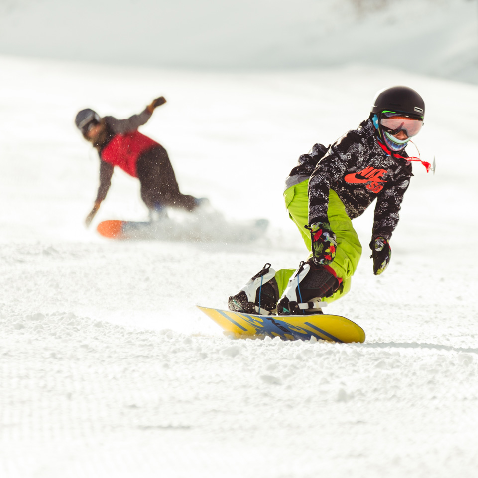 two snowboarders riding down a ski slope