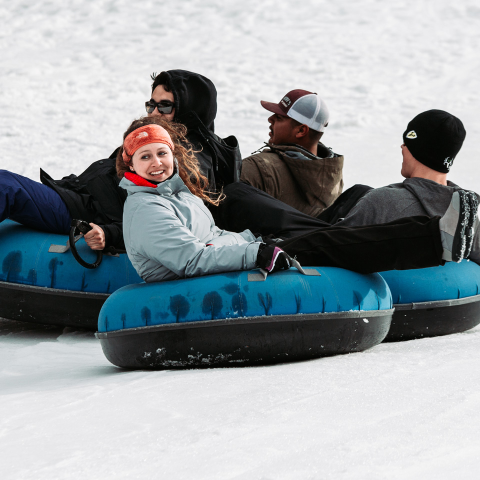 group of people snow tubing down a slope