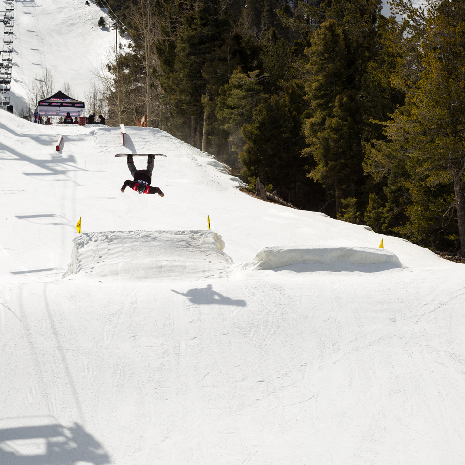 snowboarder doing a backflip on a jump